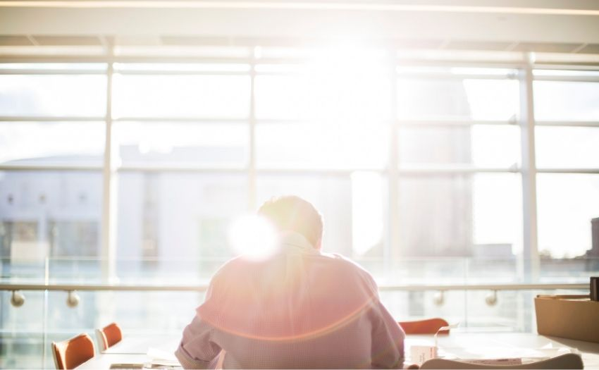 man sitting at a table with sunlight streaming in the window